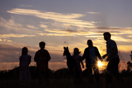 Silhouette image of family in meadow in Wendover Buckinghamshire with dog jumping by Sarah Greer