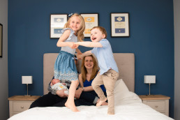 Children jumping on bed in family photoshoot with Sarah Greer in Buckinghamshire Wendover