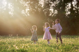 3 Children blowing dandelion clocks during natural family photoshoot in Wendover Buckinghamshire by Sarah Greer Photography